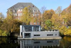 Hausboot am Eilbekkanal - am Ufer in Hamburg Uhlenhorst das Gebäude der Hochschule für Bildende Künste am Lerchenfeld in Hamburg Uhlenhorst; erbaut 1911 - 1913, Architekt Oberbaudirektor Fritz Schumacher.