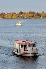Alsterschiff in Fahrt auf der Hamburger Aussenalster - die Ammersbeek fährt Richtung Lombardsbrücke / Binnenalster - im Hintergrund Herbstbäume am Ufer der Alster.