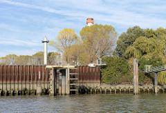 Petroleumhafen Hamburg - Eisenspundwand am Ufer - hohe Bäume mit Herbstlaub. Der Petroleumhafen soll im Rahmen der Hamburger Hafen-Westerweiterung zugeschüttet und als Container-Terminal genutzt werden. Hinter den Bäumen der Leuchtturm Oberfeuer Bube