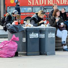 Überfüllte Mülltonnen an der Jungfernstieg-Promenade, Binnenalster Hamburg; roter Bus der Stadtrundfahrt Hamburg.