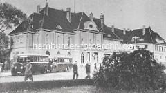 Altes Bild vom Bahnhofsgebäude in Oranienburg; Autobusse stehen auf dem Bahnhofsplatz.
