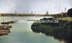 Alte Segelboote / Holzboote liegen am Steg an der Rabenstrasse, Aussenalster - im Hintergrund die Lombardsbrücke und Kirchtürme der Hansestadt Hamburg.
