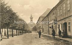 Blick durch die Meißler-Gasse in Theresienstadt zur Garnisonskirche - Strassenbäume; Geschäft für Kurzwaren und Stoffreste, Menschen vor der Eingangstür.