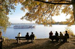 BesucherInnen in der Grünanlage am Alsterufer sitzen in der Herbstsonne auf Parkbänken unter den Bäumen am Ufer und blicken über die Aussenalster - ein Fahrgastschiff fährt auf der Alsterrundfahrt. Bilder aus dem Hamburger Stadtteil Winterhude.