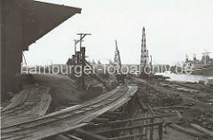 Der alte Petroleumhafen wurde ab der 1920er Jahre zum Südwesthafen umgebaut. Die Kaianlage des zukünftigen Togokais ist noch eine Baustelle. Provisorische Schienen sind auf Holzgerüsten verlegt - auf ihnen transportieren Bauloren Schutt und M