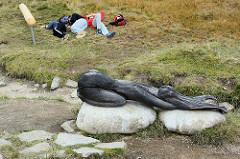 Holzskulptur an der Quelle der Elbe - nackte Frau als Symbol des fliessenden Wassers - Jugendliche liegen ermattet vom Aufstieg zur Elbquelle im Gras und ruhen sich aus.