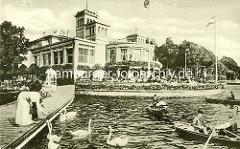 Blick vom Bootssteg zum Uhlenhorster Fährhaus - eine Frau mit Blumen am Strohhut füttert die Schwäne, der Mann mit Melone sieht zu - Gäste sitzen an Tischen auf der Terrasse am Wasser, Ruderboote. Alte Bilder aus dem Stadtteil Hamburg Uhlenhorst,