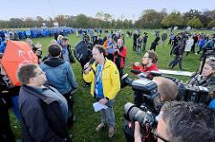 Der Moderator Frederik Braun  diskutiert mit Gegnern der Hamburger Olympiabewerbung im Hamburger Stadtpark.