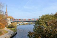 Hochbahnbrücke über den Mundsburger Kanal beim Kuhmülenteich in Hamburg Uhlenhorst, Hohenfelde; lks. der Kirchturm der St. Gertrud Kirche.