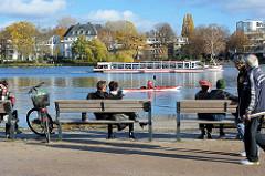 Alsterufer an der Binnenalster in Hamburg Rotherbaum - Holzbanke am Wasser, Kanu und Alsterschiff in Fahrt.