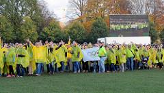 BefürworterInnen der Olympischen Spiele für Hamburg bilden im Stadtpark die Olympischen Ringe - auf einer Grossbildleinwand wird das Spektakel übertragen.