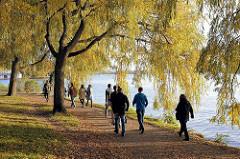 Sonntagsspaziergang im Herbst unter Herbstbäumen in der Sonne an der Alster - Alsterufer in Hamburg Winterhude, Bellevue.