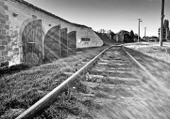 Bahngleise - geöffnete Türen von Kasematten der Festungsanlage Theresienstadt / Terezin. Kolumbarium, in dem die Asche Toter Häftlinge in Urnen aus Pappe aufbewahrt wurden.