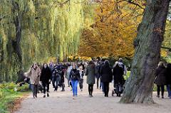 Alsterspaziergang am Sonntag Nachmittag in der Herbstsonne unter Herbstbäumen an der Hamburger Aussenalster.
