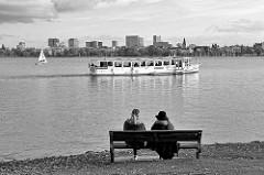 Binnenalster bei Hamburg Rotherbaum - zwei Frauen sitzen auf einer Bank und blicken auf die Binnenalster - ein Alsterschiff fährt Richtung Binnenalster.