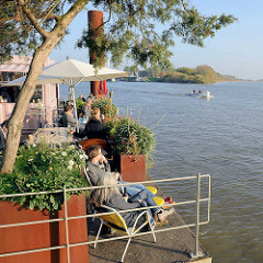 Blick auf die vorbeifahrenden Boote vom Café Entenwerder in Hamburg Rothenburgsort am Ufer der Norderelbe.