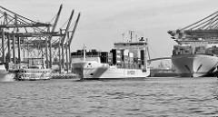 Der Containerfeeder Bianca Rabow  läuft aus dem Waltershofer Hafen aus; lks.  Containerbrücken am Terminal Burchardkai, darunter ein Raddampfer der Hamburger Hafenrundfahrt - re. der Containerfrachter Edith Maersk unter den Containerbrücken.