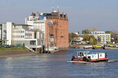Ein Schubschiff fährt in die Billwerder Bucht in Hamburg Rothenburgsort ein  - am Ufer ein historisches Speichergebäude / Industriearchitektur.