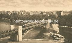 Historische Aufnahme der Kühmühlenbrücke in Hamburg Uhlenhorst - ein Hochbahn fährt auf der Brücke, darunter ein Alsterdampfer am Anleger - im Hintergrund Häuser in Hamburg Hohenfelde.