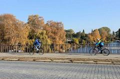 Braune Brücke über die Bille / Grenze zwischen Hamburg Hamm + Rothenburgsort; herbstliche Bäume am Flussufer, Fahrradfahrer.