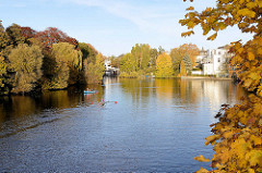 Herbst in der Hansestadt Hamburg, Herbstbäume am Ufer vom Langen Zug an der Hamburger Aussenalster - im Hintergrund der Mühlenkamper Anleger in Hamburg Winterhude.