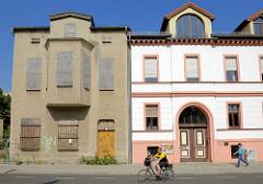 Alt + neu; Wohnhaus mit Rauhputzfassade und zugenagelten Fenstern - daneben ein restauriertes Gründerzeitgebäude mit farblich abgesetzter Fassade.