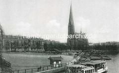 Ein Alsterdampfer fährt in den Kuhmühlenteich ein - Schuten mit Ladung liegen am Kai, Pferdefuhrwerke sollen beladen werden; dahinter die St. Gertrudkirche und Wohnhäuser in Hamburg Uhlenhorst.
