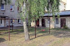 Hinterhof mit Kinderspielplatz, Teppichstangen und Schuppen in Oranienburg.