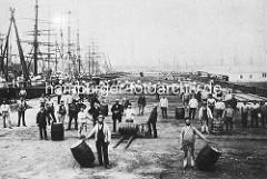 Alte Ansicht vom Hamburger Petroleumhafen auf dem Grasbrook - Segelschiffe, Frachtschiffe liegen am Kai - Arbeiter mit Fässern, in denen das Petroleum transportiert wurde. Im Hintergrund Schiffsmasten auf der Elbe und gestapelte Tonnen.