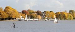 Blick über die Aussenalster ins herbstliche Hamburg Uhlenhorst - goldener Herbst mit prächtig gefärbten Bäumen an der Aussenalster beim ehem. Uhlenhorster Fährhaus - Segelboote und Stand Up Paddling auf der Alster.