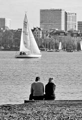 Schwarz-Weiß Fotografie von der Hamburger Aussenalster - ein Paar sitzt am Ufer der Alster und sieht den Segelbooten zu.