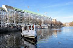 Alsterdampfer St. Georg am Anleger Jungfernstieg - im Hintergrund das Hotel Vier Jahreszeiten und Gebäude am Neuen Jungfernstieg. Das Alsterdampfschiff St. Georg ist das älteste noch fahrtüchtige Dampfschiff Deutschlands und wurde 1876 auf der Reiher