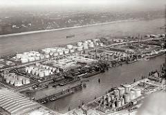 Luftfoto des Hamburger Petroleumhafens auf Waltershof - am Kai liegen Tanker, ihre Ladung wird gelöscht; An Land sind sind Benzin-Fässer aufgestapelt und warten auf den Abtransport. Auf vier Bahngleisen stehen zwischen den Tanklagern Tankwaggon