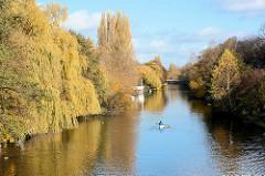 Herbst in der Hansestadt Hamburg - Herbsbäume am Ufer vom Goldbekkanal in Hamburg Winterhude - Kanu auf dem Wasser.