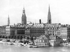 Alstes Bild vom Alsterpavillion an der Binnenalster - Alsterdampfer liegen am Steg; hinter den Geschäftshäusern der Turm vom Hamburger Rathaus und der Kirchturm der St. Katharinenkirche und St. Nikolaikirche.