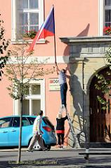 An einem Amtsgebäude in Terezin / Theresienstadt wird die Flagge der Tschechischen Republik in die Halterung gesteckt.
