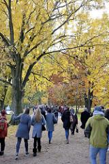 Alsterspaziergang am Sonntag Nachmittag in der Herbstsonne unter goldgelben Herbstbäumen an der Hamburger Aussenalster.