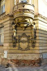 Erkerfenster - Stuckdekor mit Figuren - abgeblätterter Putz, Ziegelsteine; historische Architektur in Terezin, Theresienstadt.