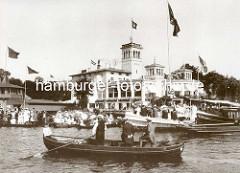Regatta auf der Hamburger Aussenalster - beim Uhlenhorster Fährhaus ist das Schild Ziel angebracht - dicht besetzte Ruderboote mit Frauen und Männern.