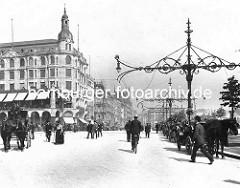 Historischer Blick in den historischen Jungfernstieg. Fussgänger und Fahrradfahrer - Pferdekutschen, weit ausladende Kandelaber  mit schmiedeeisernem Dekor als Strassenbeleuchtung.