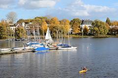 Blick von der Krugkoppelbrücke auf die Hamburger Aussenalster und dem Segelboothafen an der Fernsicht, ein Kanu / Kajak fährt Richtung Alsterkanal. Im Hintergrund Stadtvillen an der Bellevue in Hamburg Winterhude.