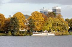 Der historische Alsterdampfer St. Georg auf Rundfahrt um die Hamburger Aussenalster - Bäume mit goldenem Herbstlaub am Ufer - Hochhäuser der Hamburger Strasse.