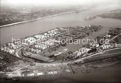 Blick über den Petroleumhafen Waltershof; ein Tanker liegt im Hafenbecken und wird gelöscht. Auf dem gesamten Hafengelände stehen unterschiedlich grosse runde Tanks., Auf der gegenüber liegenden Seite der Einfahrt des Tankhafens der Parkhafen mit