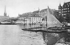 Hamburger Binnenalster am Jungfernstieg - Bootsverleih mit Ruderbooten und Segelboot unter Segeln. Gebäude vom Alsterpavillion und Geschäftshäuser am Jungfernstieg - lks. der Kirchturm der St. Petrikirche.