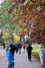 Herbststimmung an der Hamburger Aussenalster - Jogger und Spaziergänger auf dem Alsterwanderweg.