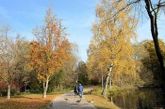 Herbstspaziergang zwischen herbstlichen Bäumen an der Wandse im Eichtalpark von Hamburg Wandsbek.