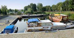 Marina an der Havel in Oranienburg - Motorboote liegen geschützt im Hafenbecken - im Hintergrund ein Wohnmobilstellplatz.