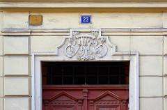 Jugendstildekor - florale Element über dem Türsturz einer Eingangstür in Terezin, Theresienstadt.