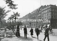 Fussgänger / Fussgängerin auf dem Jungfernstieg in der Hamburger Innenstadt / Neustadt. Fahrradfahrer und Kfz auf der Strasse - Palmen in Töpfen vor dem Alsterpavillion.