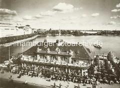 Luftaufnahme vom Alsterpavillion am Jungfernstieg an der Hamburger Binnenalster - ein Alsterdampfer fährt zum Anleger. Die Gäste vom Alsterpavillion sitzen an Tischen im Freien am Jungfernstieg.